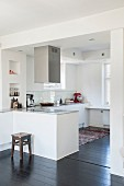 Open-plan white kitchen with counter and stainless steel extractor hood