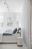 Bed with grey bed linen, round bedside cabinet on castors and floor-length curtains in bedroom