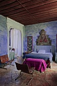 Rustic Mediterranean bedroom with religious painting on blue-painted wall, double bed and retro leather chairs