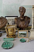 Ceramic ornaments and wooden bust of woman on surface