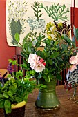 Blumenstrauss in grüner Vase auf Tisch, im Hintergrund Bild mit nostalgisch gezeichneten Pflanzenabbildungen