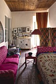 Pink sofa opposite daybed with ethnic blanket in eclectic ambiance