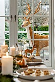 Fake reindeer outside French windows seen over set table