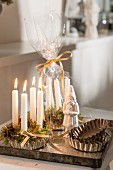 Lit white candles and moss in tart cases next to Father Christmas figurine and set of tart cases