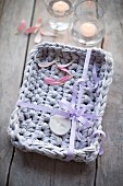 Crocheted basket made from lilac Zpagetti yarn decorated with ribbon and gift tag as a gift