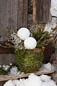 Twigs and Christmas baubles in plant pot wrapped in moss