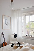 White wooden chair and guitar next to lattice window in bright bedroom with rustic charm