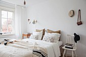 Scatter cushions and blanket on double bed, stacked books on white chair used as bedside table with hat on backrest in simple bedroom