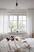 Off-white bedspread on bed below lattice window in rustic bedroom