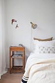 Schlichter Nachttisch aus Holz neben Bett, darüber Wanddeko mit Vogelmotiv und Wandleuchte