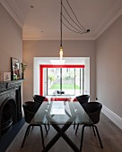 Light-bulb pendant lamp above glass table and black shell chairs in modernised interior with red steel structure seen through wide, open doorway in background