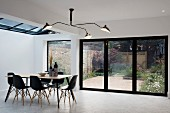 Three-armed ceiling lamp, dining table and black shell chairs in front of terrace doors
