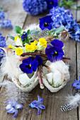Eierschalen mit Hornveilchen, Schlüsselblumen und Federn gefüllt