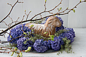 Easter lamb cake in nest of hyacinths and thyme with budding lime branches