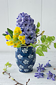 Hyacinths, cowslips and twigs of young lime leaves in vase