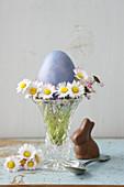 Vase mit Gänseblümchen und einem Osterei, daneben Schokoladeosterhase