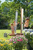 Children playing under outdoor shower in garden