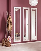 Three narrow mirrors with hand-made frames painted white on dusky pink wall