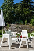 White plastic outdoor easy chairs on sunny wooden deck in garden with boulders in background