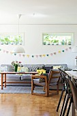 Wooden armchair and matching exotic-wood table below bunting on wall below transom windows