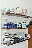 Crockery in various patterns stacked on retro String shelves