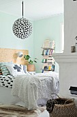 Graphic patterns and pastel turquoise wall in bedroom