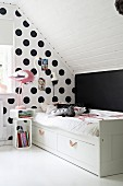 Bed against polka-dot wall in child's bedroom