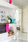 Old wood-fired cooker in white interior with splashes of bright colour