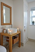 Washstand with countertop sink on wooden frame and framed mirror in rustic bathroom