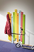 DIY children's coat rack made from wooden boards painted in bright colours