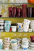 Collection of retro cups and crockery on glass shelves