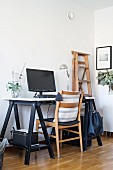 Wooden chair and desk on black wooden trestles in corner of minimalist room