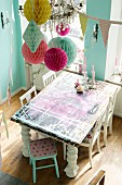 Table with various layers of paint and white wooden chairs below colourful paper pompoms