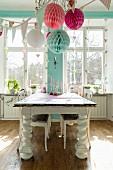 Holztisch mit massiven, gedrechselten Tischbeinen im Esszimmer, romantisch mit Papier-Pompons und Girlanden dekoriert