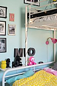White metal bunk beds, decorative letters and framed photos of children on pale blue wall