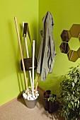 DIY coat rack made from broom handles, metal bucket and pebbles