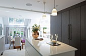 Glossy white island counter and dark brown fitted cupboards in elegant, open-plan kitchen