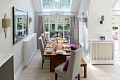 Elegant set dining table with pale upholstered chairs in niche with skylight