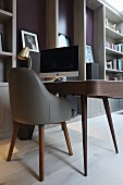 Monitor on elegant desk, grey retro leather chair and floor-to-ceiling shelving