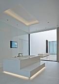 Freistehende Badewanne mit Stufe, in weißem, minimalistischem Designerbad mit indirekter Beleuchtung im Boden- und Deckenbereich,