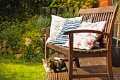 Colourful scatter cushions on garden bench