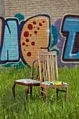 Alte Stühle mit neu bezogenen Sitzpolstern auf der Wiese, im Hintergrund Graffiti an Wand