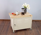 Breakfast and flowers on locker with castors and wooden top