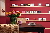 CDs on DIY shelves on claret-red wall seen across backrest of wicker chair