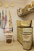 Wicker baskets on vintage cabinet, storage baskets on wall-mounted shelf, aprons and laundry basket in rustic room
