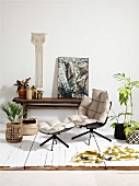 Designer armchair and footstool with pale upholstery amongst house plants