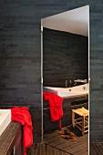 Mirrored door in bathroom with dark wall tiles