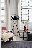 Studio lamp next to armchair and side table in living room