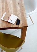 Notebook and smartphone on wooden table with shell chairs