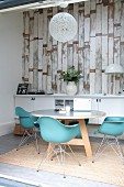 Classic turquoise shell chairs at round table in front of white sideboard against wallpaper with pattern of vintage wooden boards